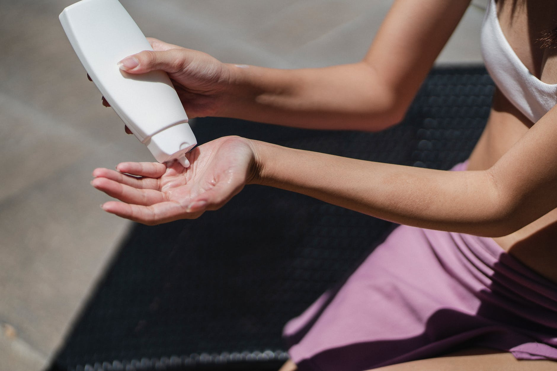 faceless woman applying lotion on hand on sunny day